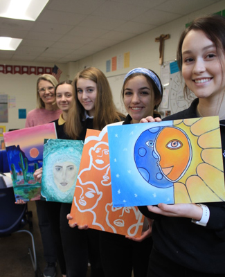 Students holding their paintings
